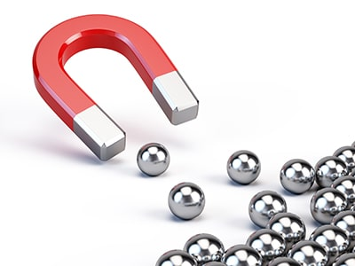 A magnet attracting ball bearings.